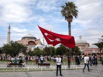 ISTANBUL, TURKEY - JULY 15: A man waves Turkey's national flag in front of the Hagia Sophia Mosque on the fourth anniversary of the July 15, 2016 failed coup attempt on July 15, 2020 in Istanbul, Turkey. On the night of July 15, 2016, 249 people died when military personnel attempted to overthrow the government and President Recep Tayyip Erdogan.  (Photo by Chris McGrath/Getty Images)